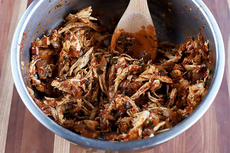 Horizontal image of shredded chicken mixed in a red sauce.