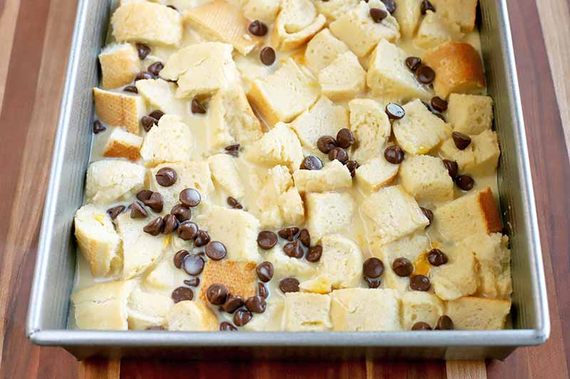 Closely cropped overhead horizontal shot of a metal baking pan of bread cubes soaking in an egg mixture and sprinkled with chocolate chips, on a wood surface.