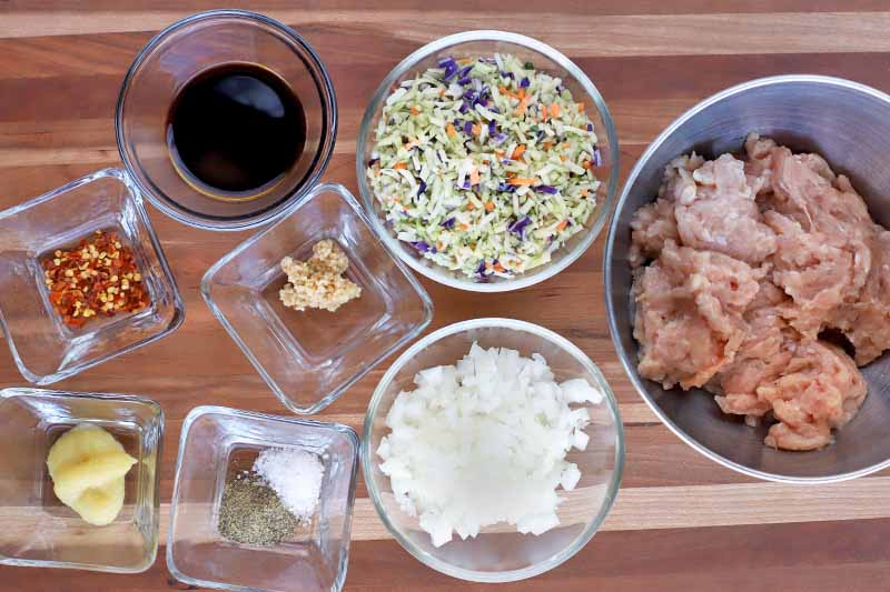 Overhead shot of four square and three round glass bowls of soy sauce, chopped vegetables, salt, and spices, and a stainless steel bowl of raw ground chicken, on a striped beige and light brown wood surface.