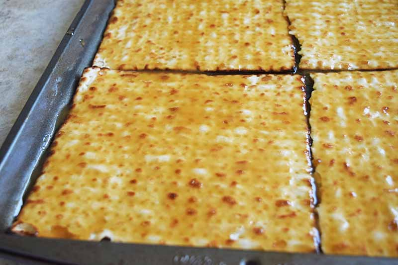 Caramel sauce spread on pieces of matzo in a metal baking pan.