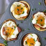 Horizontal image of a muffin tin with baked breakfast cups, with whole eggs, ground pepper, bacon, and white bread.