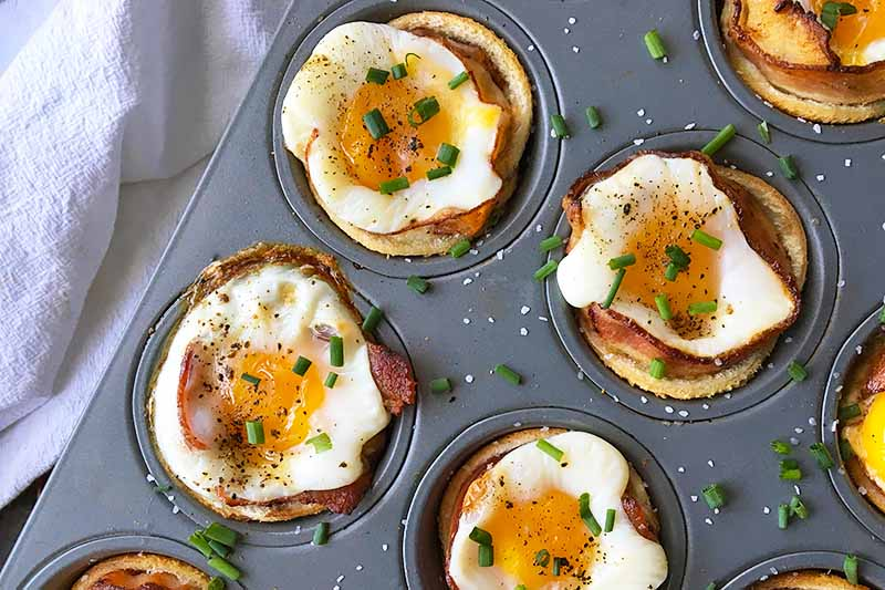 Horizontal image of a muffin tin with baked breakfast cups, with whole eggs, ground black pepper, bacon, and white bread.