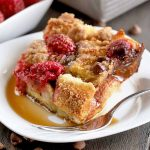 Horizontal image of a portion of homemade French toast casserole on a white plate with a fork, in a pool of maple syrup, on a dark brown wood surface with two white square dishes in the background, one of which is filled with fresh raspberries, and scattered chocolate chips strewn across the tabletop.