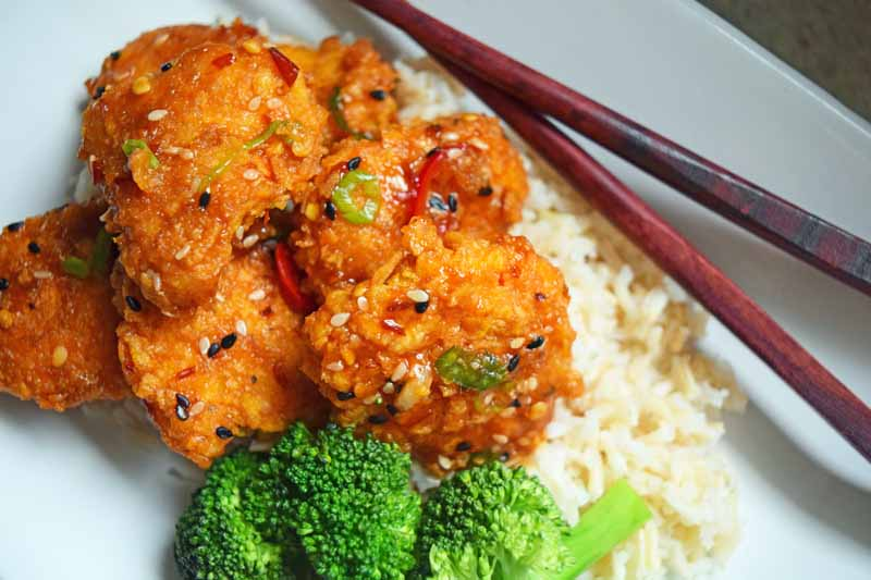A white porcelain plate with baked General Tso's chicken, rice, broccoli, and a pair of chopsticks.