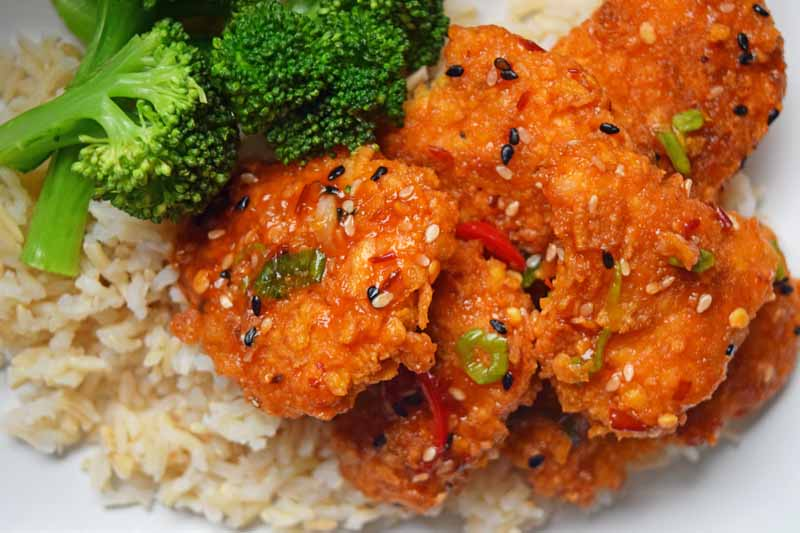 Close up of General Tso's chicken with steamed broccoli and rice.