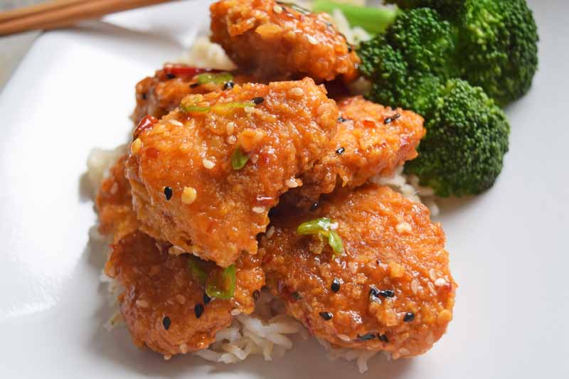 Baked and lightened up General Tso's chicken on a white ceramic plate.