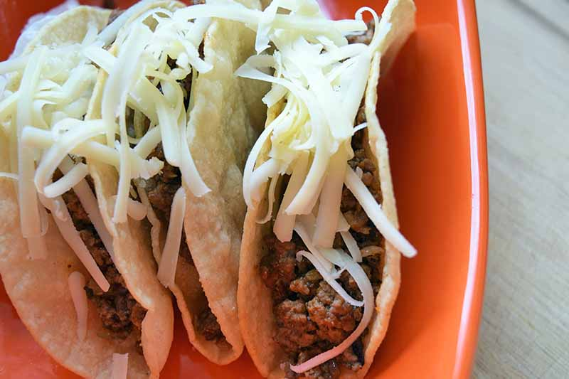Horizontal closely cropped overhead shot of an orange ceramic baking dish filled with hard shell tacos standing upright, with shredded whtie cheese on top, on a gray surface.