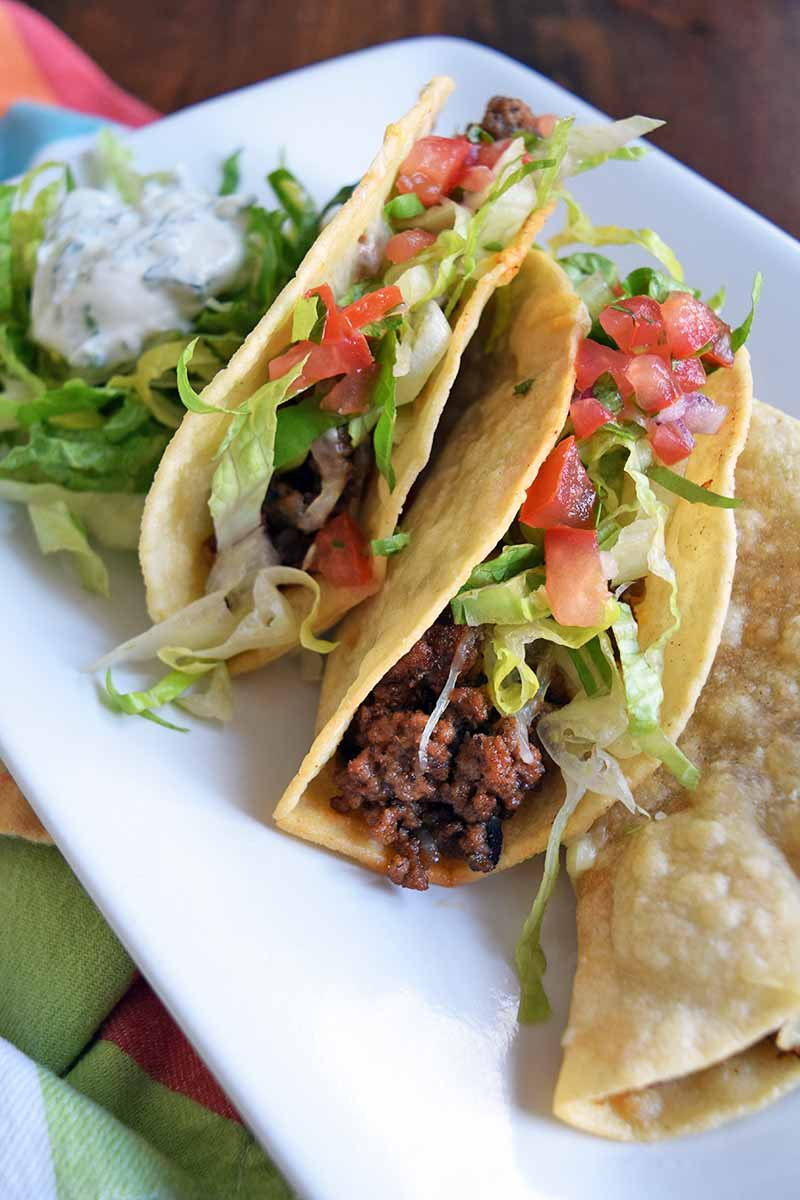 Vertical overhead shot of beef tacos on a white serving platter, with shredded lettuce and diced tomato on top, on a brown wood surface topped with a folded multicolored cloth.