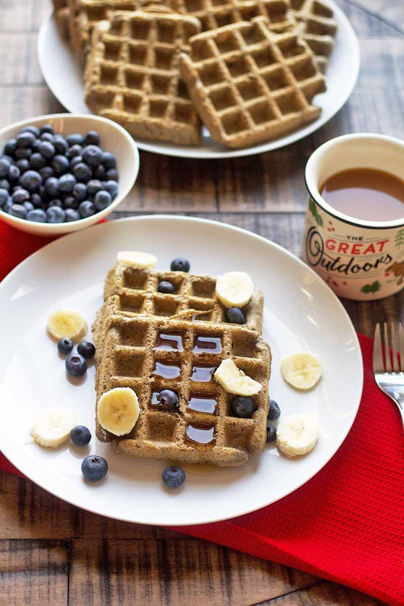 Overhead image of two white plates of waffles, one with syrup, sliced banana, and berries on top, with a small white bowl of fresh blueberries to the left and a cup of coffee to the right, on a red cloth on top of a brown wood table.
