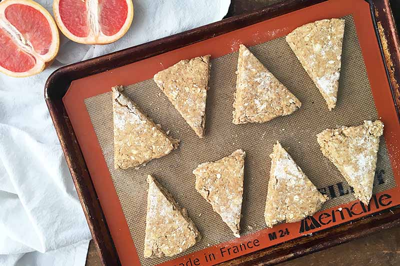 Horizontal image of unbaked portioned dough triangles on a silicone mat on a sheet pan.