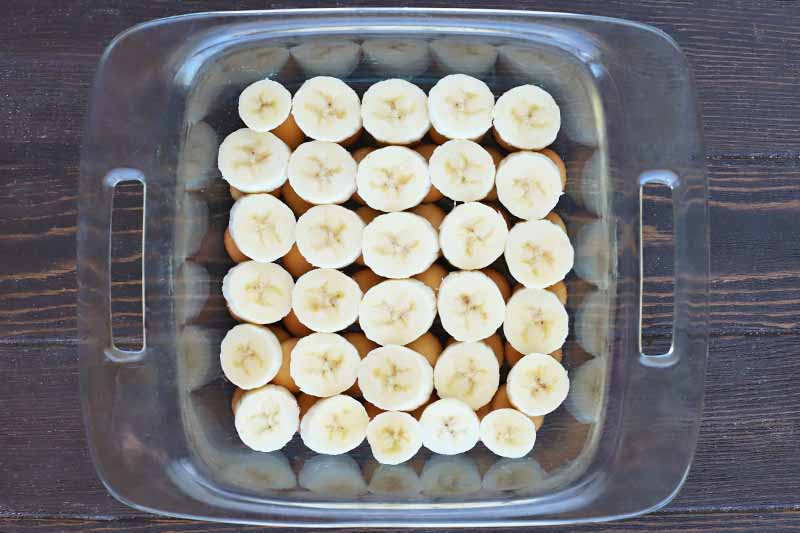 Overhead horizontal shot of banana slices arranged on top of wafer cookies in even rows, in a glass baking dish with handles, on top of a dark brown wood table.