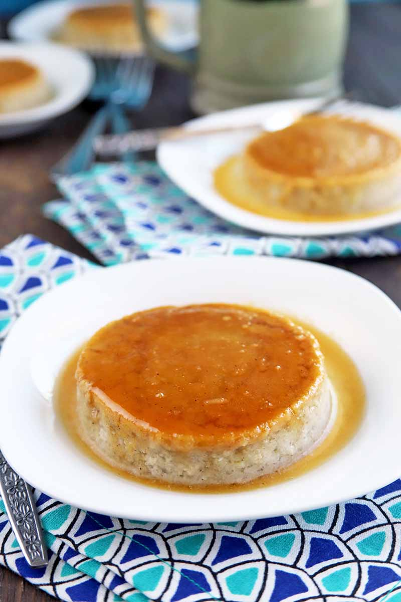 Vertical oblique shot of two white plates of homemade flan, with two more beside a