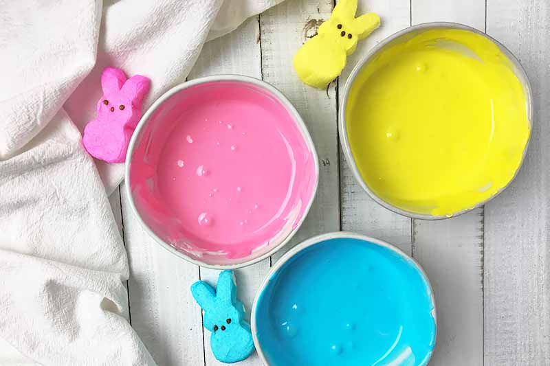 Horizontal image of three bowls filled with assorted colored royal icing next to Peeps on a white board and white towel.