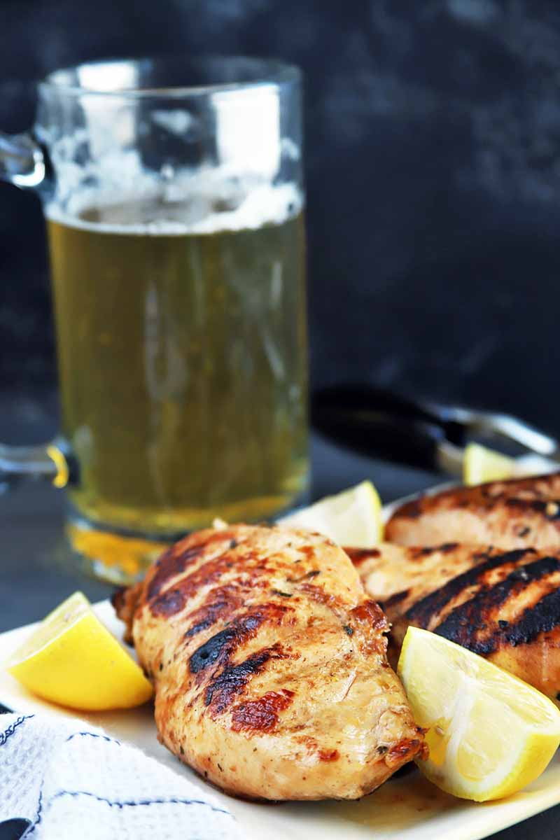 Vertical image of a mug of beer and a plate of grilled chicken with lemon wedges, on a white cloth with blue stripes on a gray slate surface, with a black mottled background.