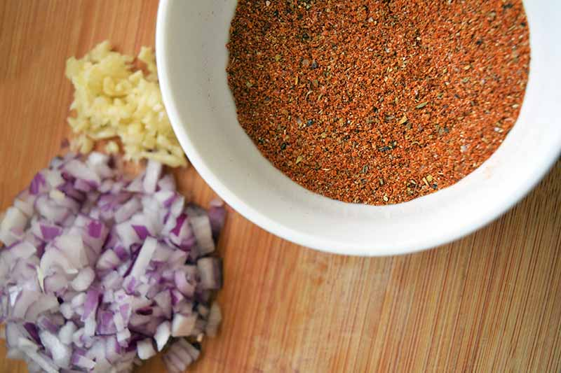 Closely cropped overhead horizontal shot of a white bowl of homemade taco spice mix to the right, and two piles of chopped red onion and minced garlic to the left, on a wooden cutting board.
