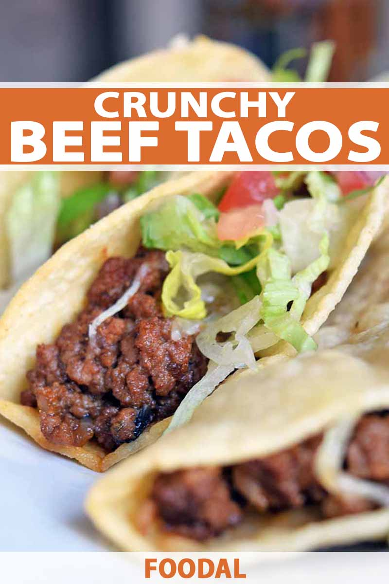 Vertical closeup image of three hard shell beef tacos with shredded lettuce, diced tomato, and melted sharp cheddar cheese, on a white plate, printed with orange and white text at the bottom and midpoint of the frame.