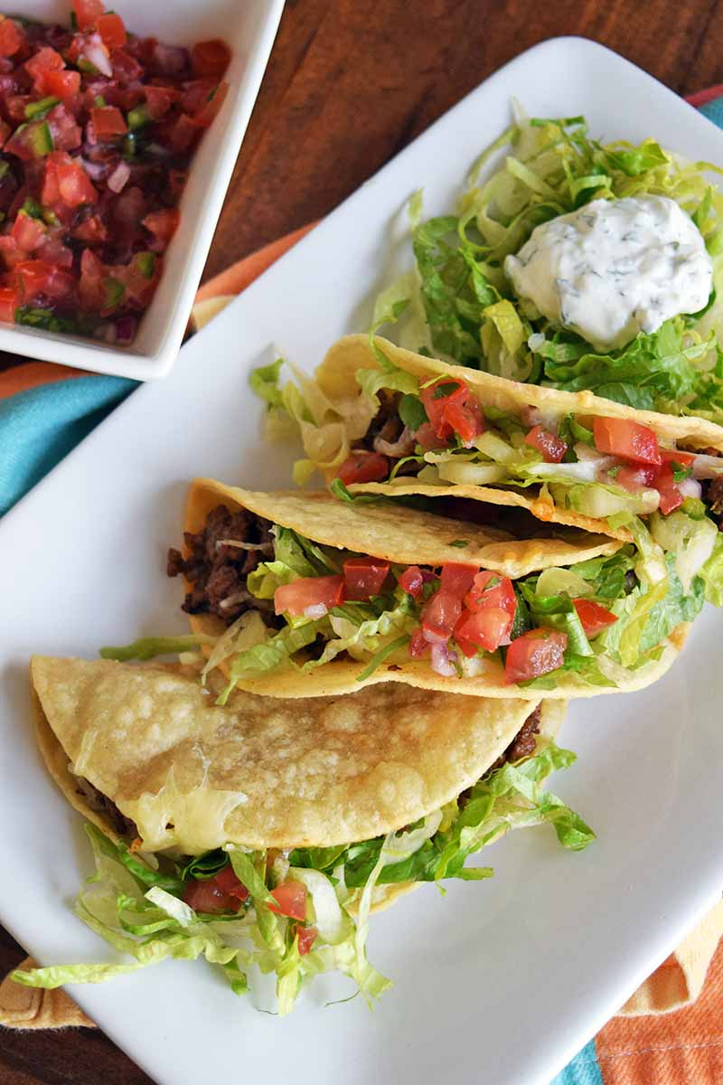 Overhead shot of three hard-shell beef tacos with lettuce and tomato, with a dollop of herb crema, and a square white dish of fresh salsa to the left, on a brown wood surface topped with a folded multicolored cloth.