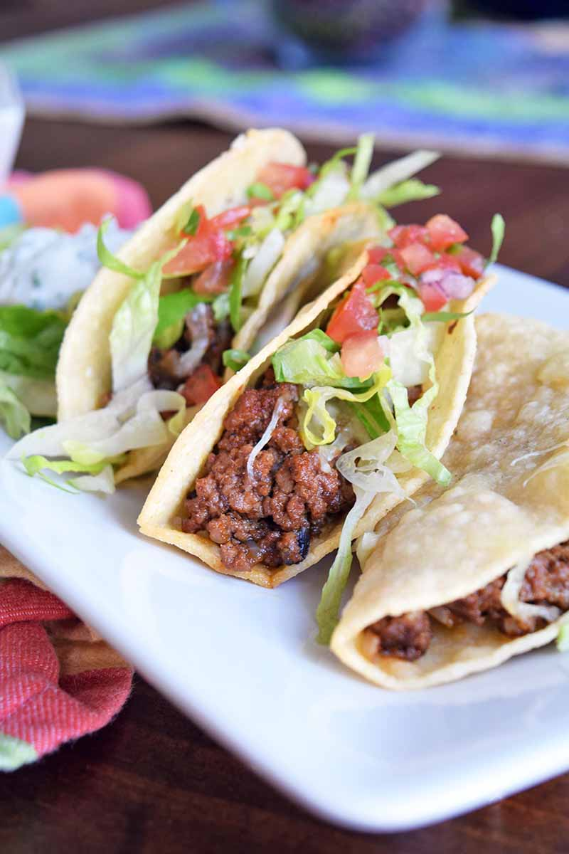 Vertical head-on shot of three beef tacos in hard corn shells with shredded lettuce, diced tomato, and melted cheese, on a brown wood table with a folded multicolored cloth, and another cloth spread out in the background.