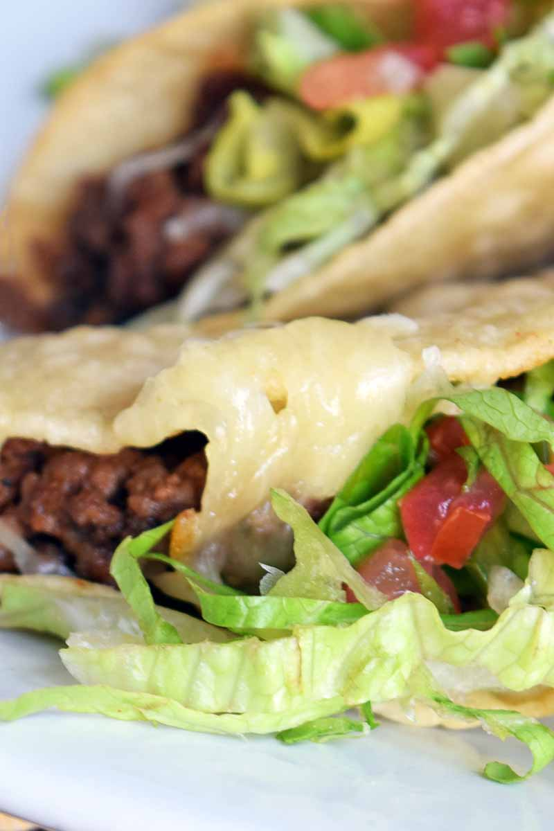 Vertical extreme closeup image of beef tacos with melted cheese, shredded lettuce, and diced tomato on a white plate.