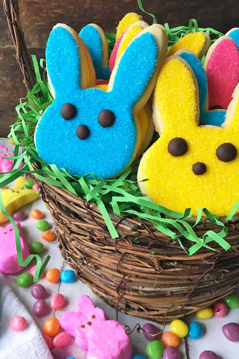 Vertical image of bunny cookies in an Easter basket with green grass next to assorted candies.