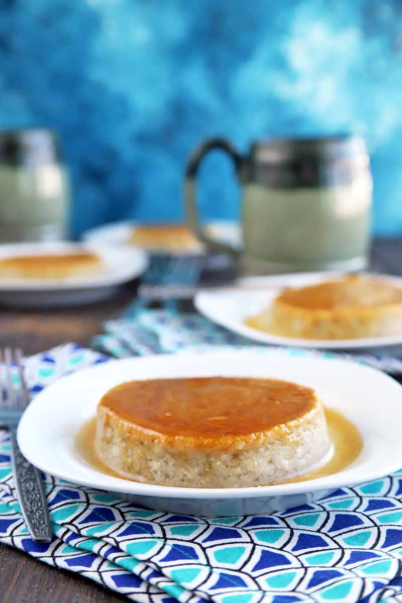 Vertical shot of three white plates of flan, with one centered and in focus at the center of the image and the others in soft focus behind it, with two dark and light gray mugs with handles, on a brown wood surface with folded patterned blue cloth napkins and forks, on a mottled blue and white background.