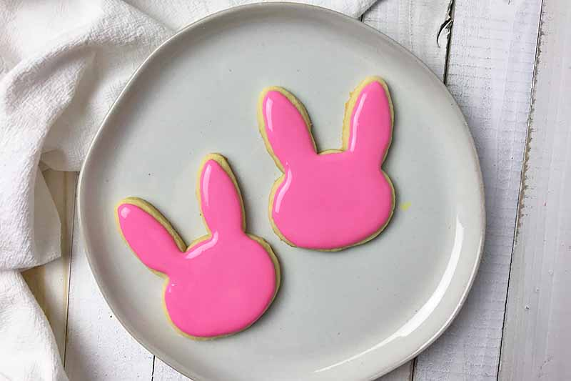 Horizontal image of two cookies with pink royal icing decorations on a white plate.