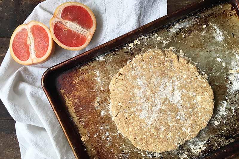 Horizontal image of a circular piece of dough on a sheet pan next to grapefruit slices.