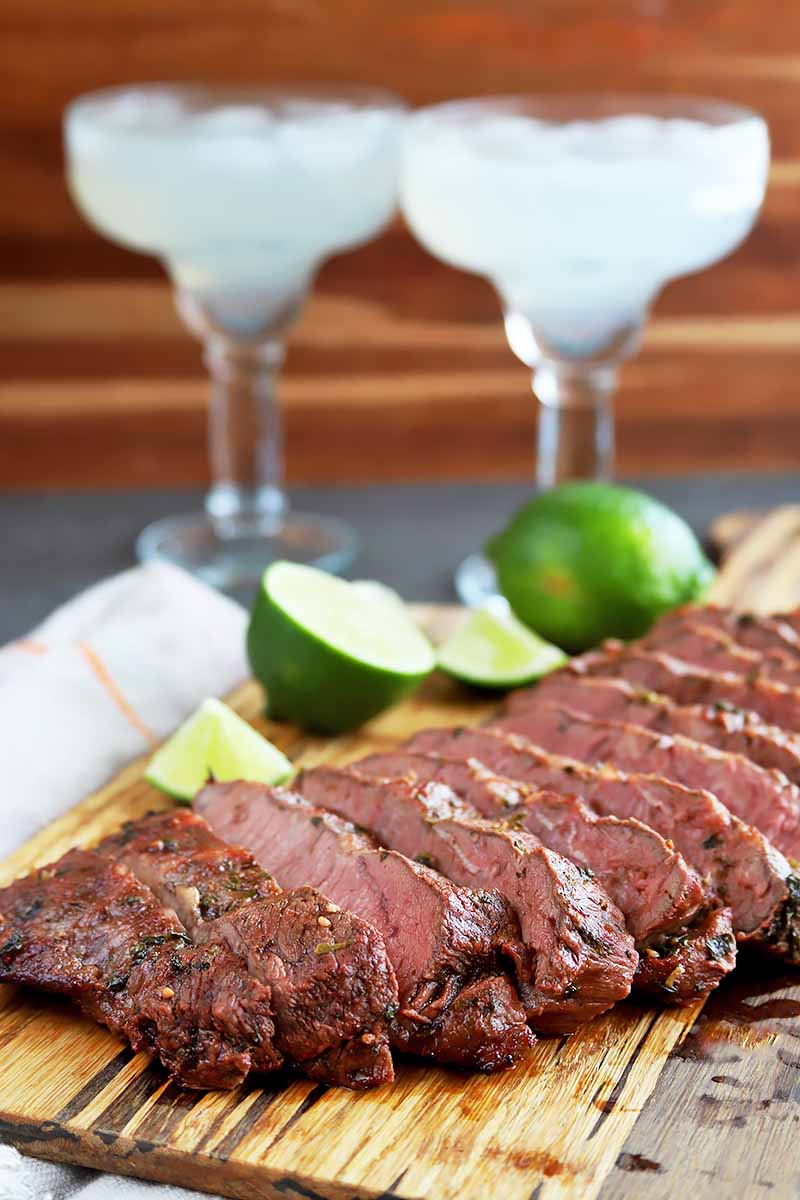 Vertical image of sliced meat on a wooden cutting board with limes, in front of two margarita glasses.