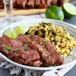 Horizontal image of a plate with corn salsa, sliced meat, and limes, in front of limes, glasses, and a cutting board with more meat.