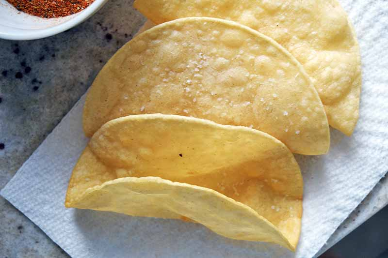Fried corn tortillas that have been shaped to make taco shells are resting on a piece of paper towel on top of a gray and white speckled granite counterop, with a small white bowl of a red spice mixture at the top left corner of the frame.