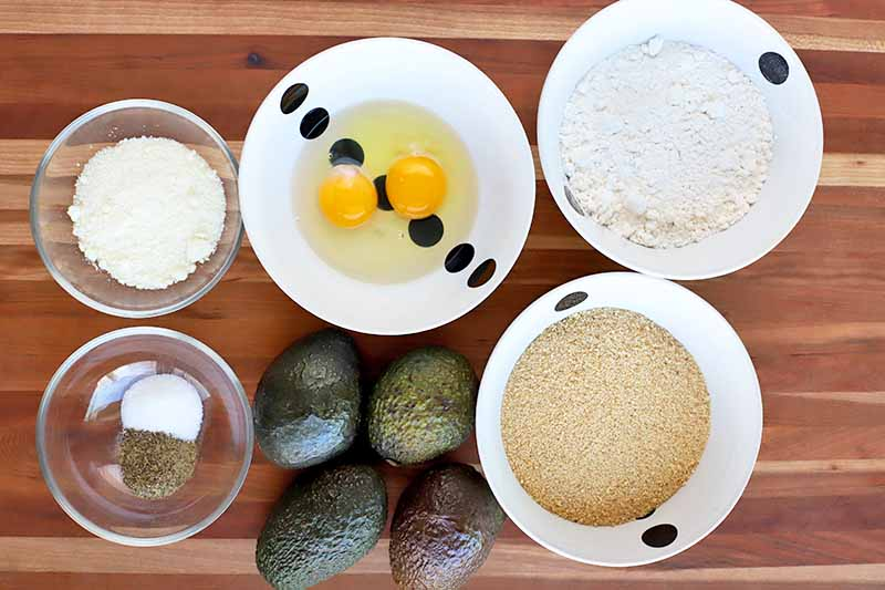 Overhead shot of three black and white and two smaller clear glass bowls filled with flour, breadcrumbs, shelled eggs, grated cheese, and salt and pepper, with four avocados on a beige and brown wood surface with horizontal stripes.