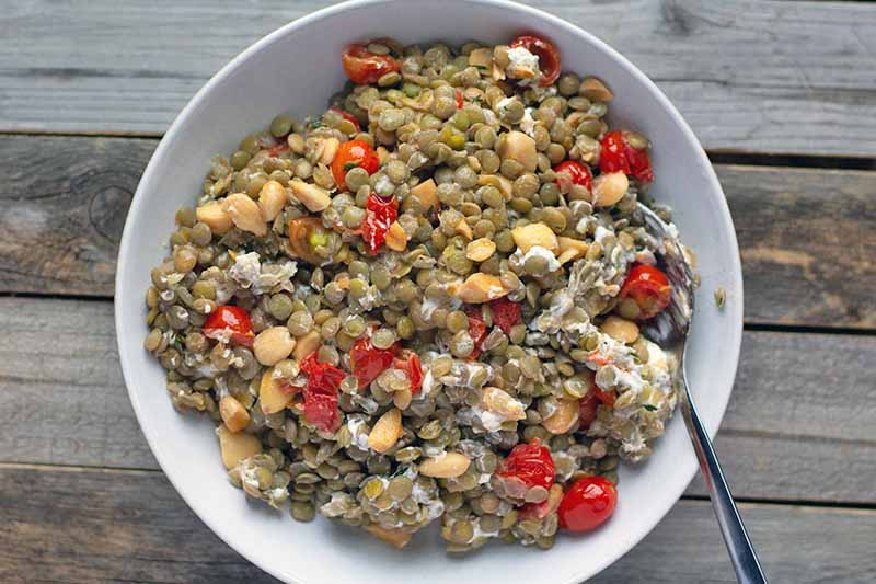 Overhead horizontal image of a white bowl of lentil salad with tomatoes, almonds, thyme, and goat cheese, with a spoon in the bowl, on an unfinished wood table.