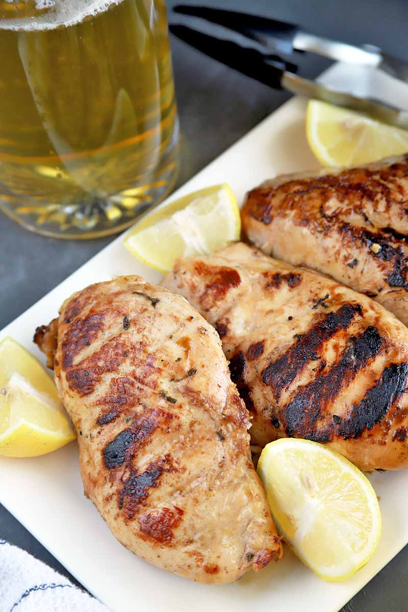 Vertical image of a white rectangular serving platter of grilled boneless, skinless poultry with metal tongs and wedges of lemon, on a gray slate surface with a white and blue striped dish cloth, and a mug of beer.