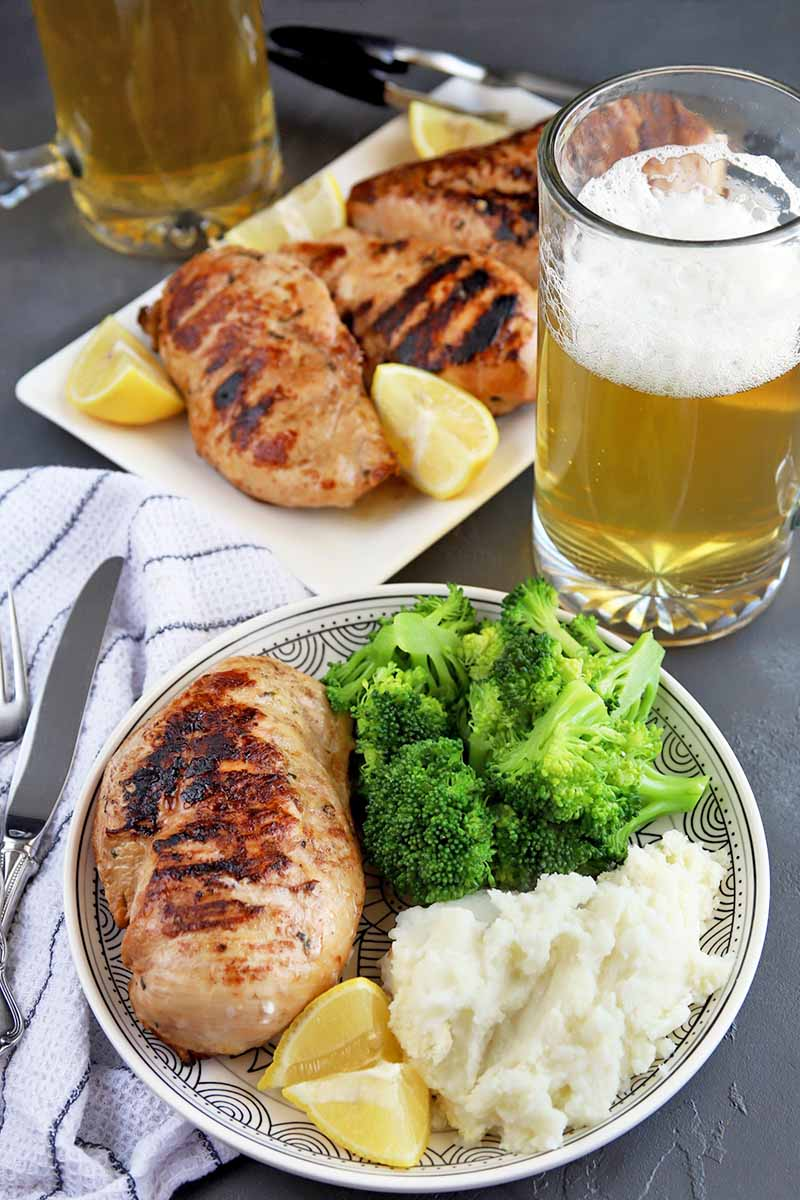 A white serving platter of grilled chicken with lemon wedges is in the background, with metal tongs and two mugs of foamy beer, with a white plate of chicken, broccoli, mashed potatoes, and cut citrus in the foreground, on a white cloth with blue stripes that is topped with a stainless steel knife and fork, on a gray slate surface.