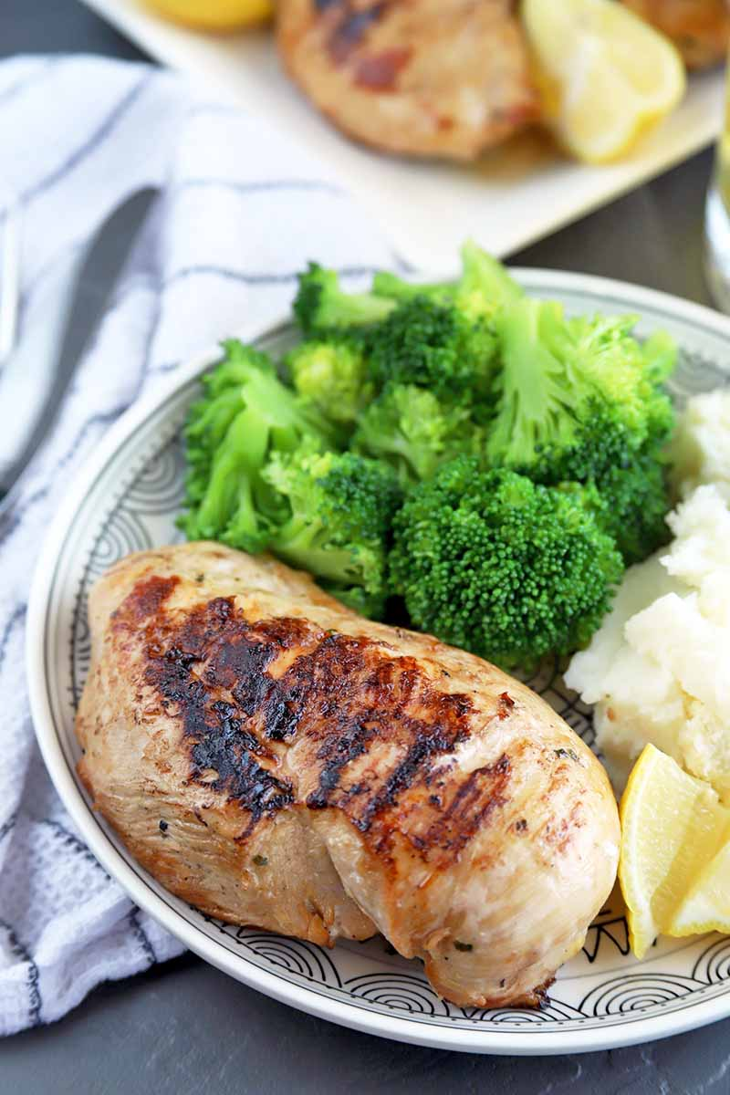 Vertical image of a white plate of grilled chicken, broccoli, and mashed potatoes, with a white cloth with blue striped topped with silverware, and a plate of more poultry in the background, on a gray slate surface.