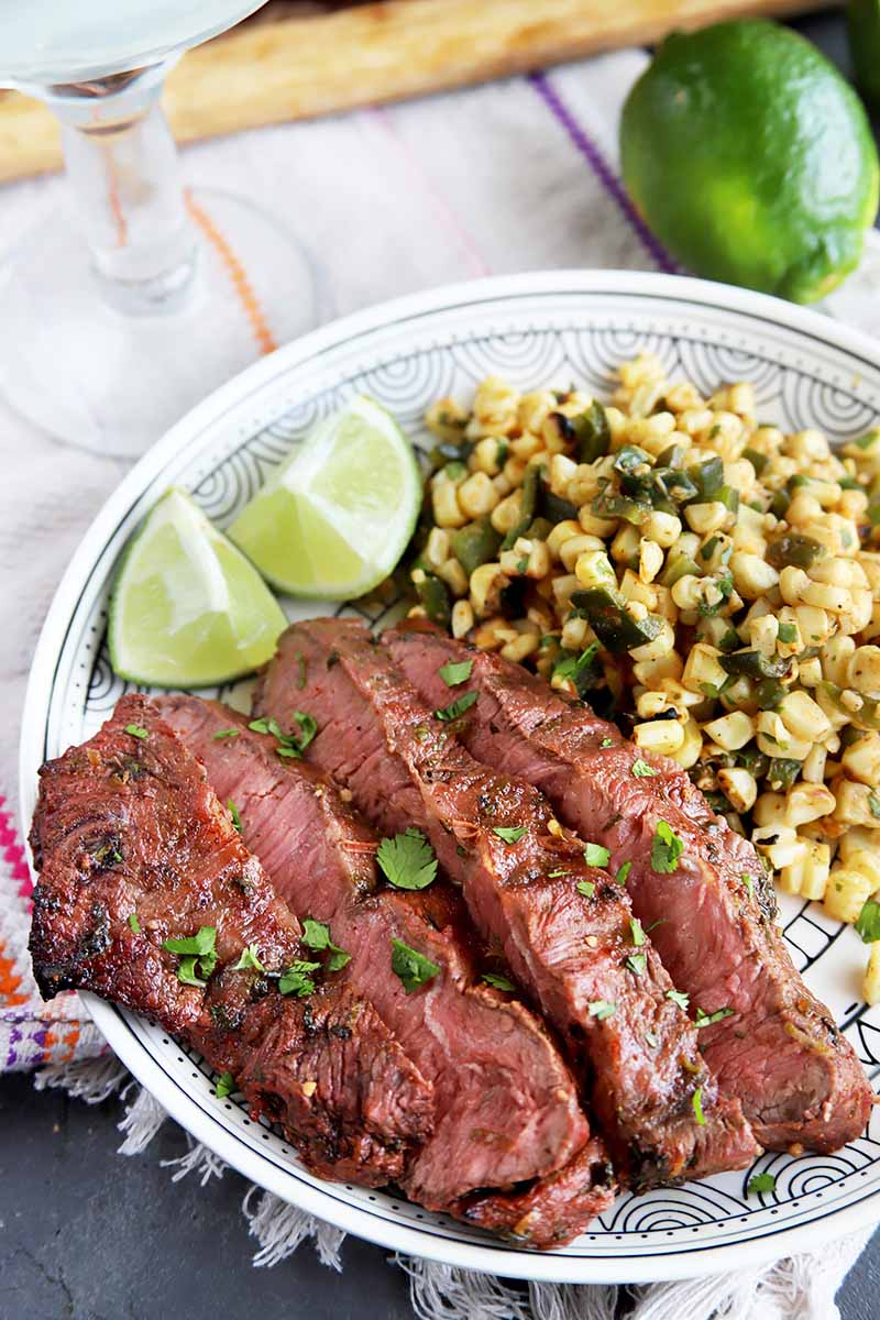 Vertical image of sliced meat, lime quarters, and corn on a plate next to a glass and a whole lime on a towel.