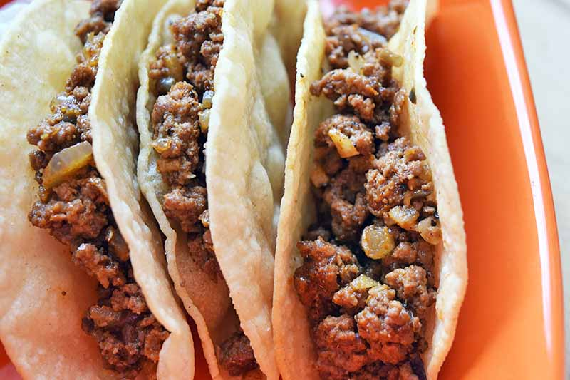 Closely cropped overhead horizontal image of three hard-shell tacos filled with a spiced ground beef mixture, arranged so they are standing upright in an orange ceramic baking dish.