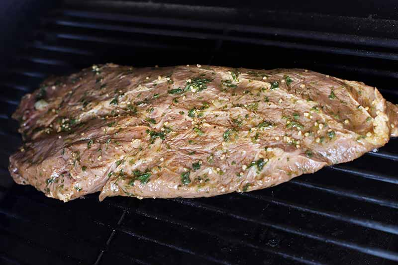 Horizontal image of a whole marinated steak on a grill.