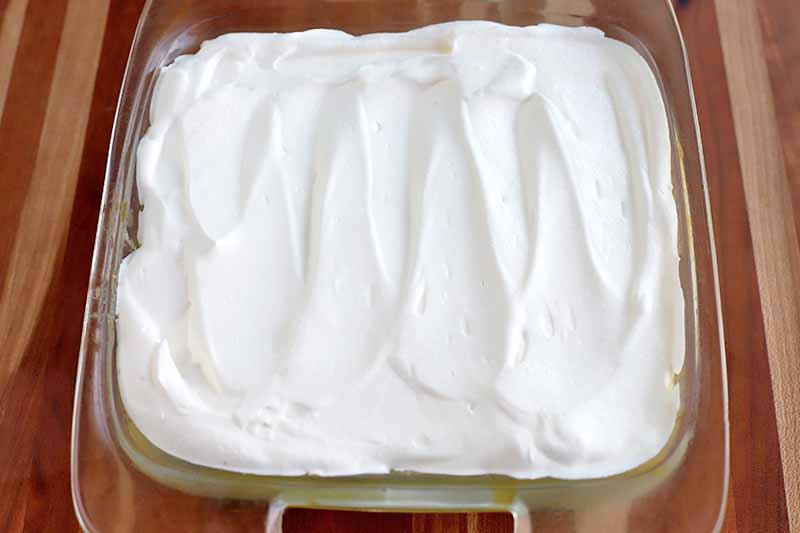 Overhead horizontal shot of a whipped cream that has been spread neatly with a spatula on top of the contents of a square glass baking dish, on a striped beige and brown wood surface.