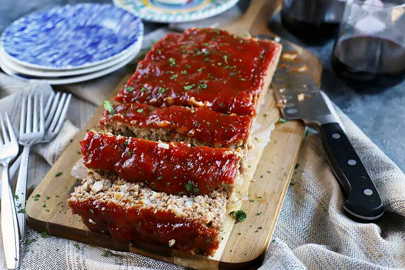 Horizontal image of a partially sliced ketchup-topped meatloaf on a cutting board.