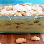 Horizontal head-on image of a glass baking dish of banana cream pudding with whipped cream on top,with scattered vanilla wafer cookies and a white cloth on a striped beige and brown wood surface, with a blue background.
