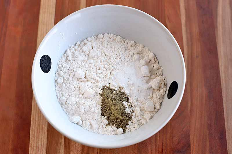 Overhead shot of a white bowl with two black spots, with flour, salt, and pepper at the bottom, on a beige and brown wood surface with vertical stripes.
