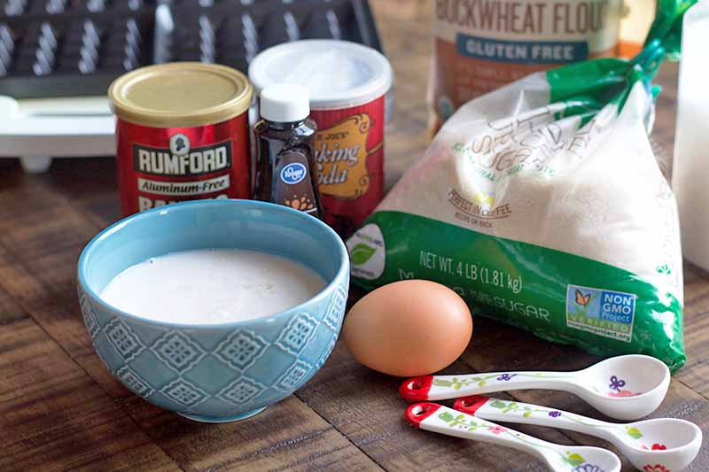 Two red canisters of baking soda and baking powder, a blue ceramic bowl of buttermilk, a brown egg, a clear and green plastic bag of sugar, three ceramic measuring spoons, and a waffle maker, o a brown wood surface.