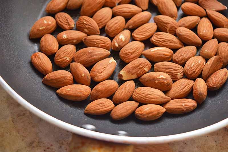 Overhead closely cropped horizontal image of whole almonds being toasted in a nonstick frying pan, on a beige surface.