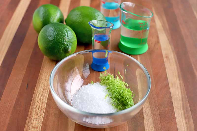 A small glass dish of coarse salt and lime zest, with three of the whole citrus fruits in the background beside green and blue measuring beakers of tequila and orange liqueur, on a brown wood surface.