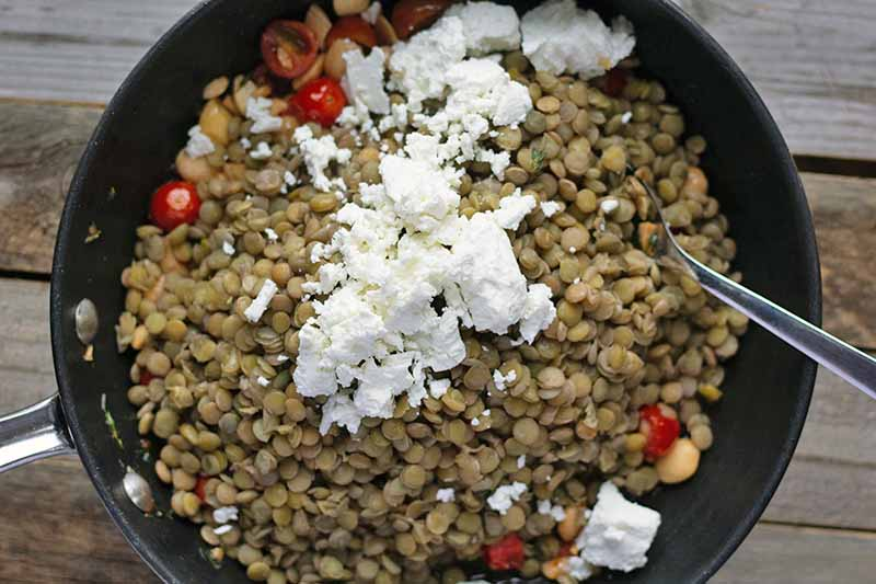 Closely cropped horizontal overhead image of a nonstick saucepan filled with cooked French green lentils, crumbled goat cheese, red cherry tomatoes that have been cut in half, and chopped blanched Marcona almonds, with a few scattered green thyme leaves, on an unfinished wood surface.