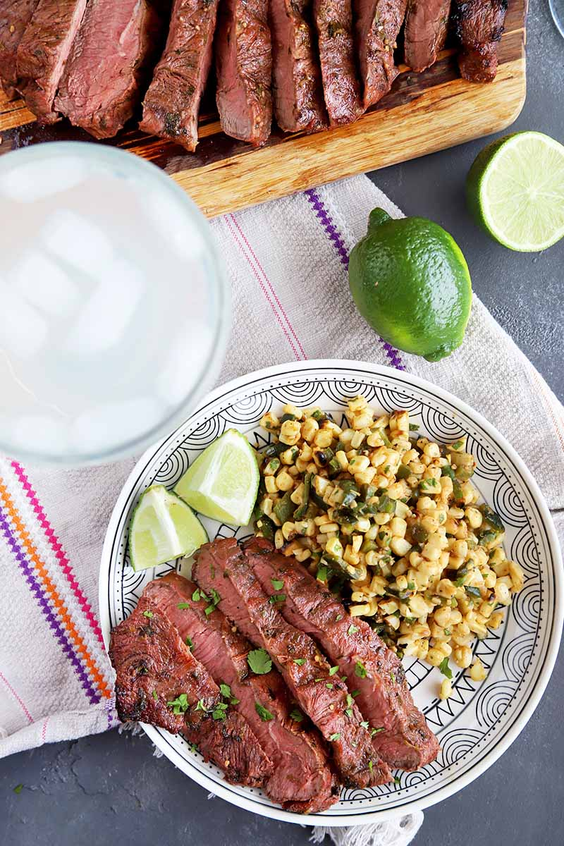 Vertical image of a plate of steak, limes, and corn on a towel next to a margarita and more sliced meat.