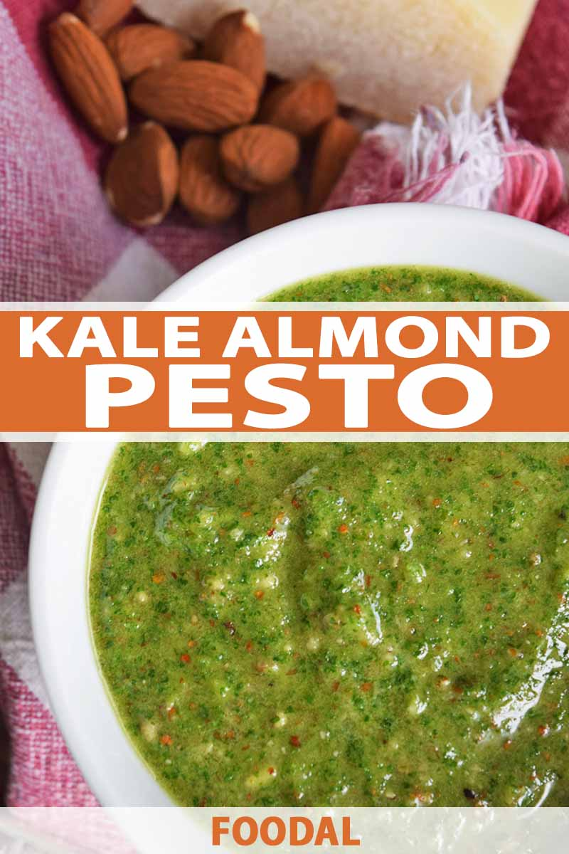 Vertical overhead closely cropped image of a white ceramic bowl of green homemade pesto, with whole almonds and a hunk of aged Pecorino cheese, on a red and white cloth, printed with orange and white text at the bottom and midpoint of the frame.
