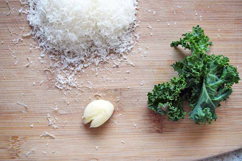 Overhead closely cropped horizontal image of a small pile of grated Pecorino cheese, a small piece of curly green kale, and a peeled and smashed whole clove of garlic, on an unfinished wood cutting board.