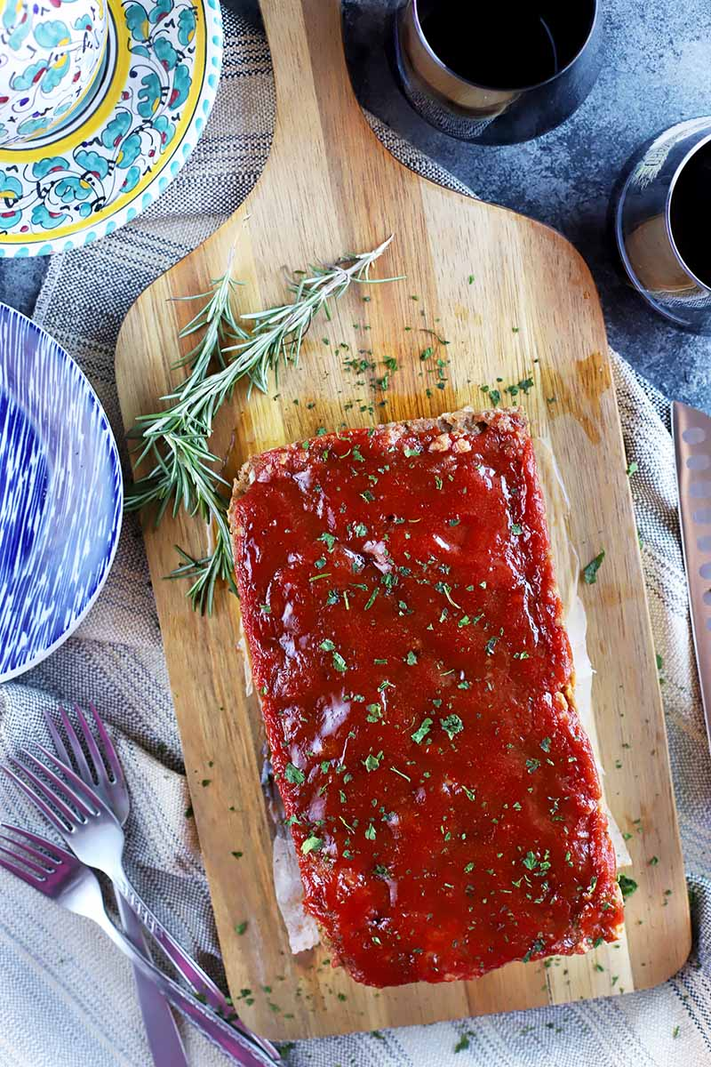 Vertical topdown image of a whole meatloaf with a ketchup glaze and herby garnish on a cutting board, next to colorful plates, a pile of forks, and glasses of wine.